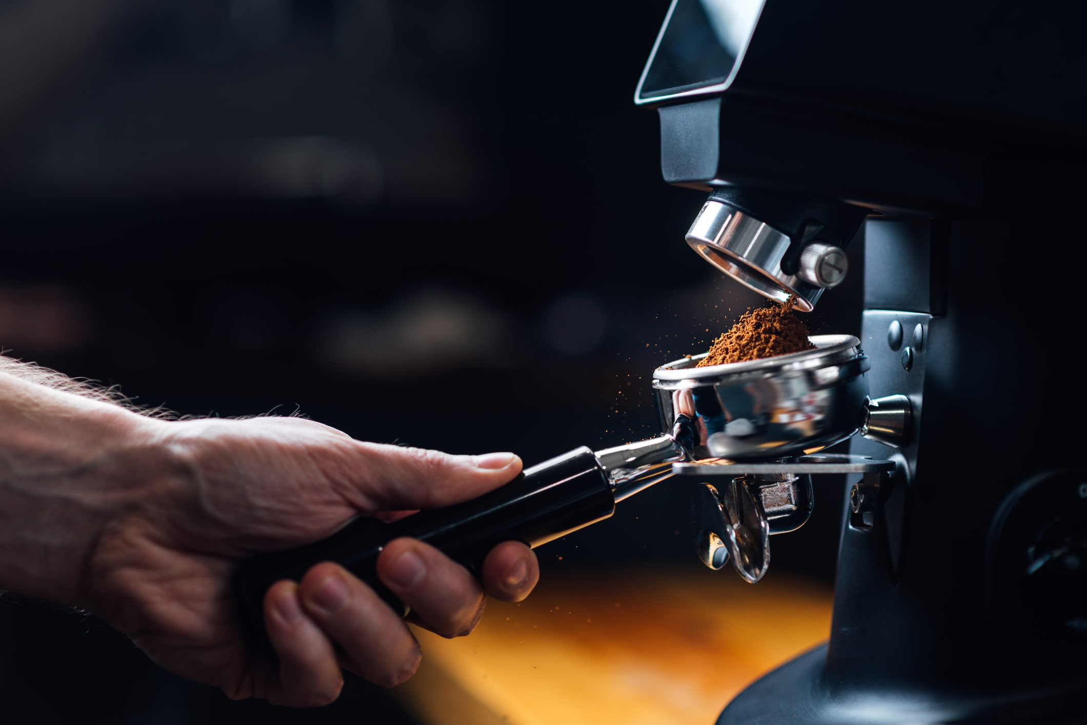 ground-coffee-pouring-into-a-portafilter-with-a-grinder-166226267-min