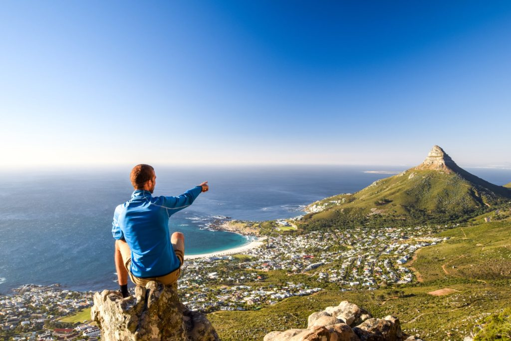 young-male-hiker-sitting-on-a-rock-at-kasteelspoort-hiking-trail-in-table-mountain-national-park-in-cape-town-108341398-min